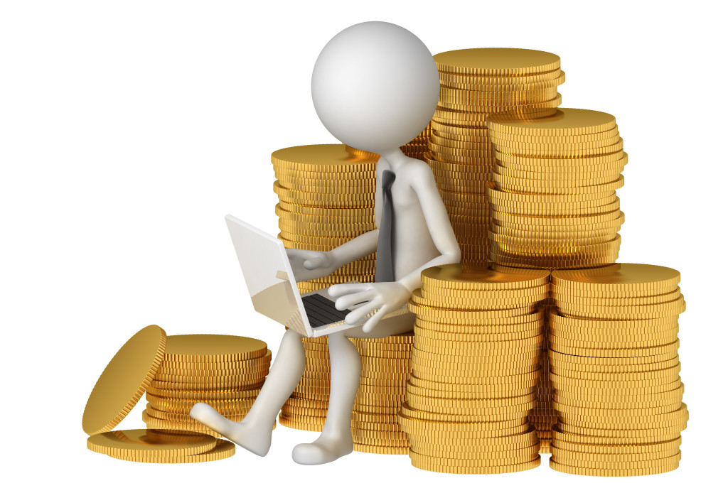 Businessman with laptop sitting on stack of coinss. E-commerce concept. Isolated