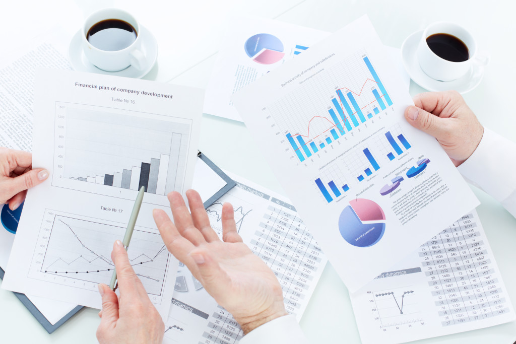 Above angle of mature business partners hands during analysis of marketing