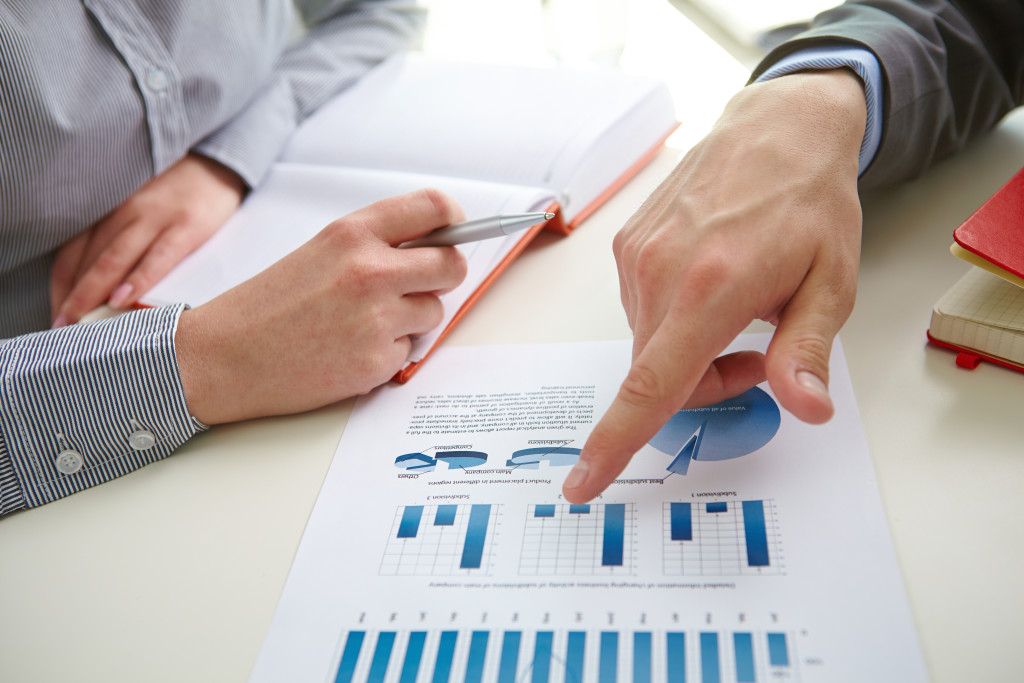 Male hand pointing at business document while explaining it